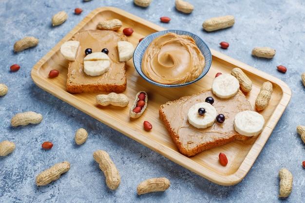 Urso engraçado e macaco enfrentam sanduíche com manteiga de amendoim, banana e groselha preta, amendoins, vista superior