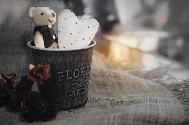 Urso fofo dos namorados com coração branco em um balde de alumínio. fundo do conceito do dia dos namorados