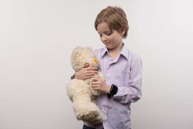 Urso fofo. menino bonito olhando para seu brinquedo enquanto o segura nas mãos