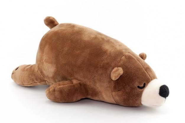 Urso marrom do brinquedo que dorme isolado no fundo branco