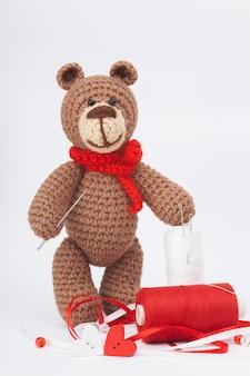 Urso marrom feito malha pequeno com objetos para o bordado. agulha, linha, miçangas. feito à mão, close-up. amigurumi