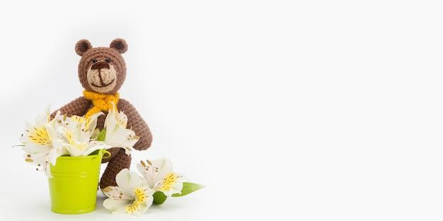 Urso marrom pequeno com flores brancas, brinquedo feito malha, feito a mão. amigurumi
