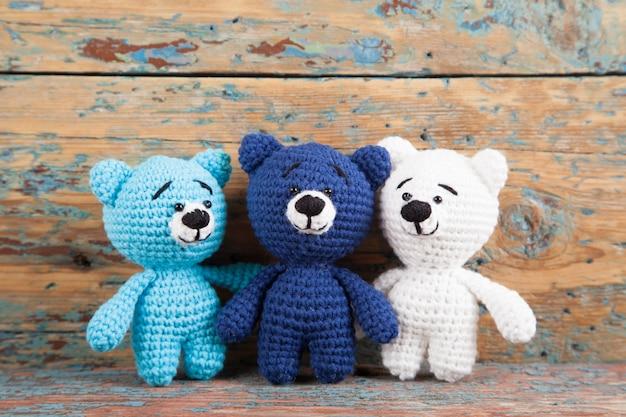 Urso pequeno de malha em um velho de madeira. brinquedo artesanal de malha. amigurumi