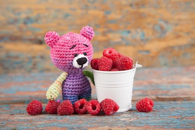Urso pequeno feito malha colorido com baga em um fundo de madeira velho. brinquedo de malha artesanal. amigurumi