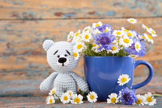 Urso pequeno feito malha com camomila em um fundo de madeira velho. brinquedo de malha artesanal. amigurumi
