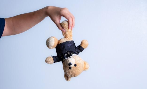Urso pequeno pendurado no fundo branco