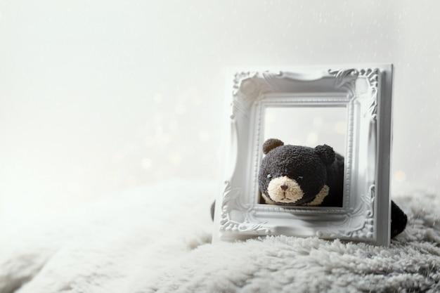 Urso preto preguiçoso segurando a moldura para retrato vazia. feliz natal conceito plano de fundo.
