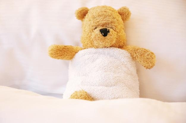 Urso usa toalha branca está na cama.
