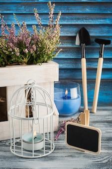 Urze rosa, vela azul acesa e ferramentas de jardinagem