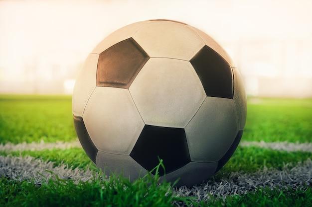 Usado bola de futebol clássico preto e branco no canto de futebol de marcação de campo sem pessoas.