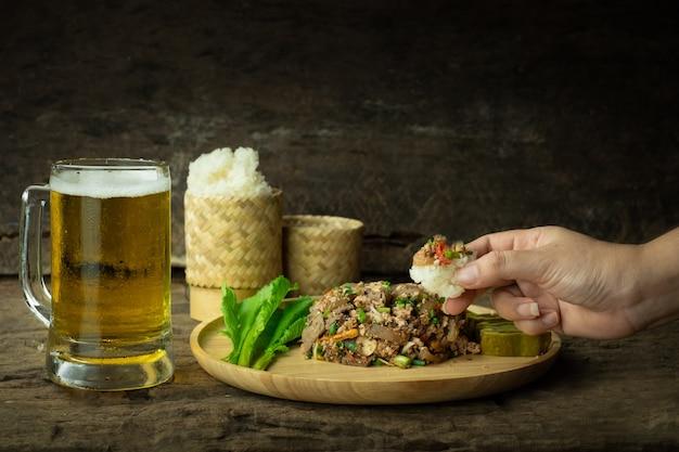 Usando a mão para comer arroz pegajoso e salada de porco picada picante com cerveja