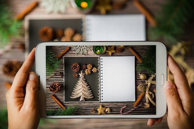 Usando a mão segurando o tablet para tirar uma foto cartão com moldura de natal