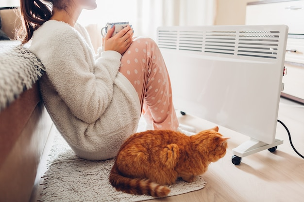 Usando aquecedor em casa no inverno. mulher aquecendo e bebendo chá com gato. estação de aquecimento.