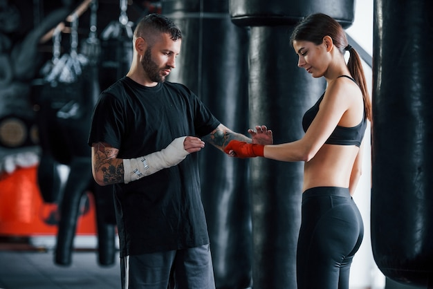 Usando bandagens. jovem treinador de boxe tatuado ensina jovem no ginásio.
