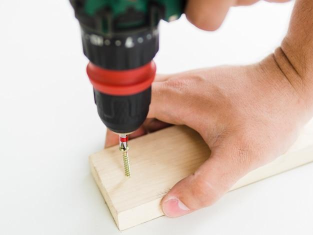 Usando de perfurador com bico na barra de madeira