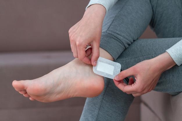 Usando emplastro adesivo médico bactericida em casa durante o uso de sapatos novos cuidados com a pele do pé e prevenção de calos e calosidades