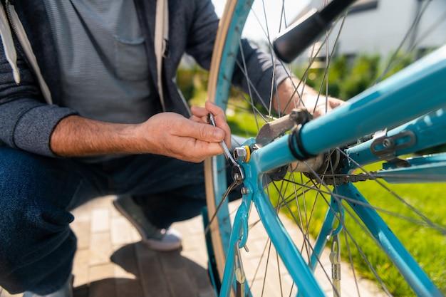 Usando equipamentos. homem forte vestindo uma jaqueta esporte azul escura usando o equipamento enquanto conserta sua bicicleta velha