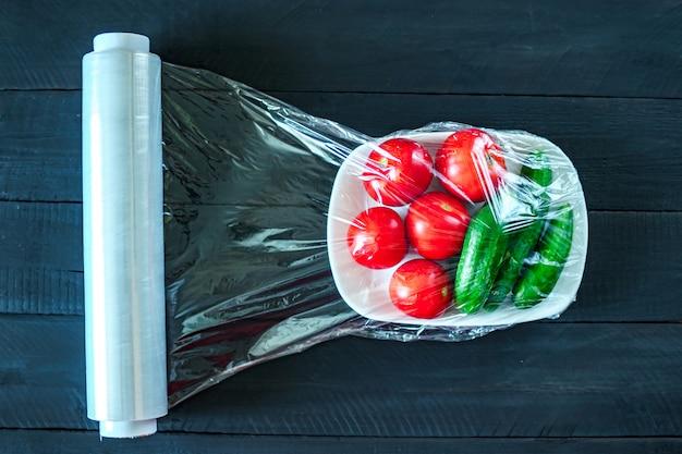Usando filme alimentar para armazenamento de legumes na geladeira. vista do topo