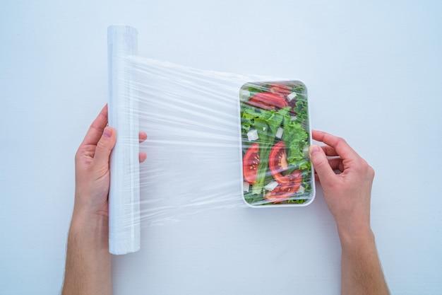 Usando filme plástico de polietileno para armazenamento de alimentos na geladeira em casa