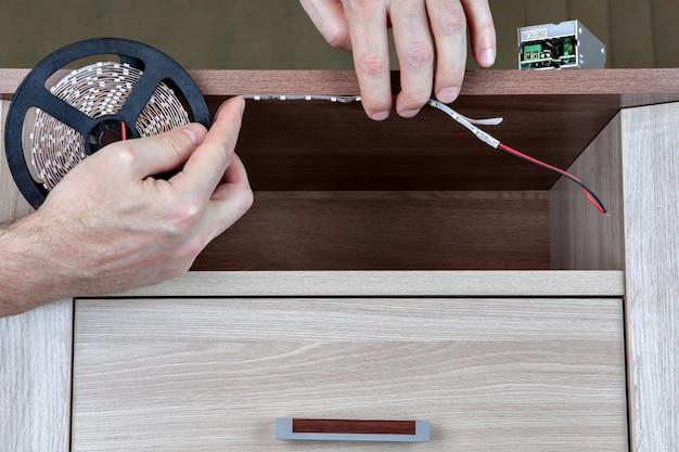 Usando fitas de iluminação led para móveis de interior, mãos humanas colaram fita adesiva a bordo.
