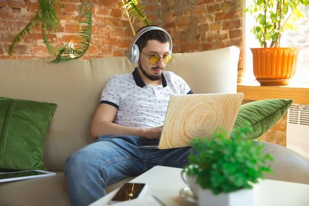 Usando gadgets. homem que trabalha em casa durante a quarentena de coronavírus ou covid-19, conceito de escritório remoto. jovem empresário, gerente fazendo tarefas com smartphone, computador, tem conferência online, reunião.