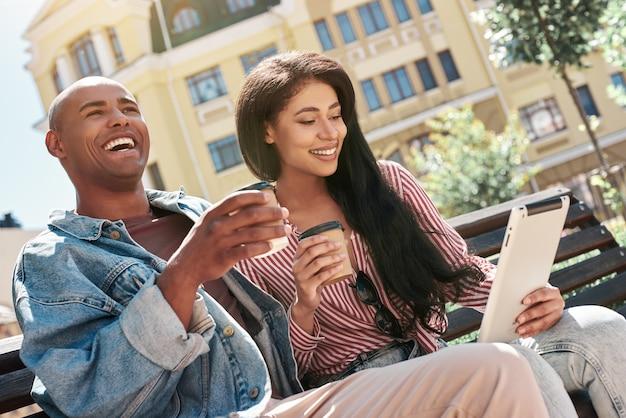 Usando gadgets, jovem casal diversificado sentado em um banco na rua segurando copos, bebendo