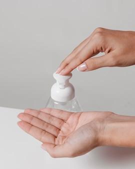 Usando gel de desinfetante para mãos hidroalcoolique vista elevada