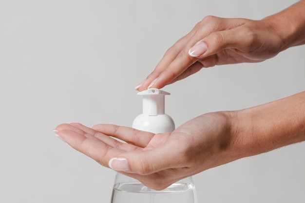 Usando gel hidroalcoolique desinfetante para as mãos, vista frontal