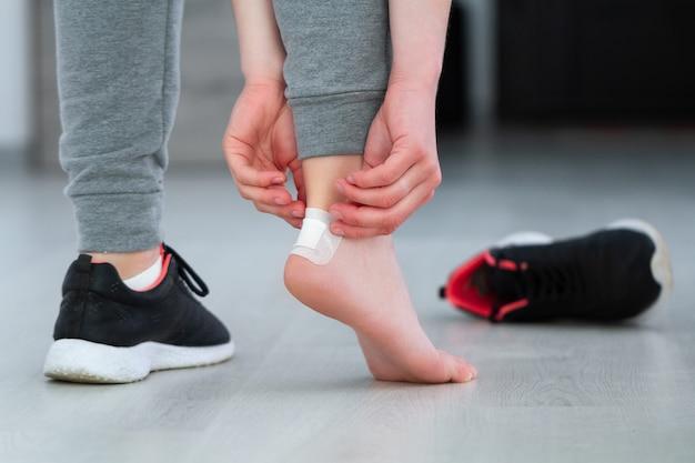 Usando gesso adesivo médico branco de calos durante o uso de um sapato novo