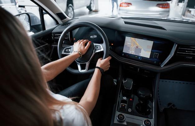 Usando gps. garota em um carro moderno no salão. durante o dia dentro de casa. comprando novo veículo