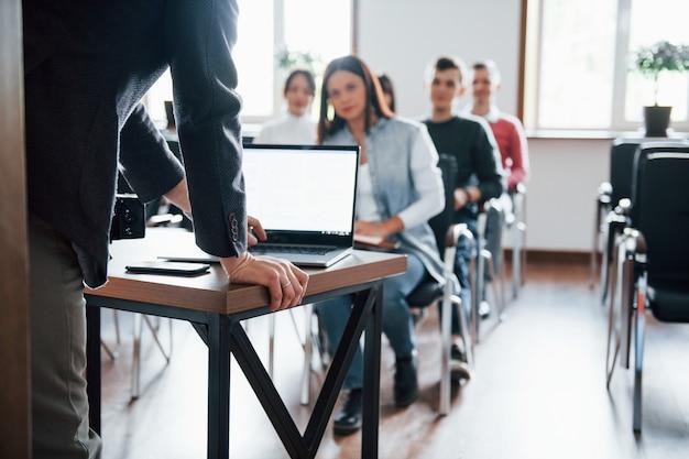 Usando laptop. grupo de pessoas em conferência de negócios em sala de aula moderna durante o dia