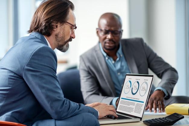 Usando laptop. homem de negócios grisalho usando óculos e usando a internet em um laptop sentado perto de um colega