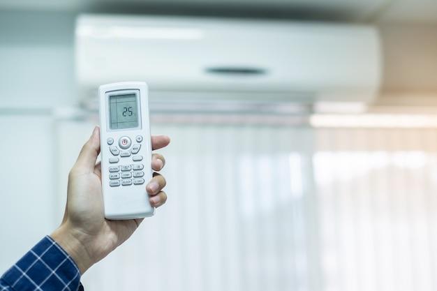 Usando o controle remoto para ajustar o ar condicionado dentro da sala do escritório ou da casa