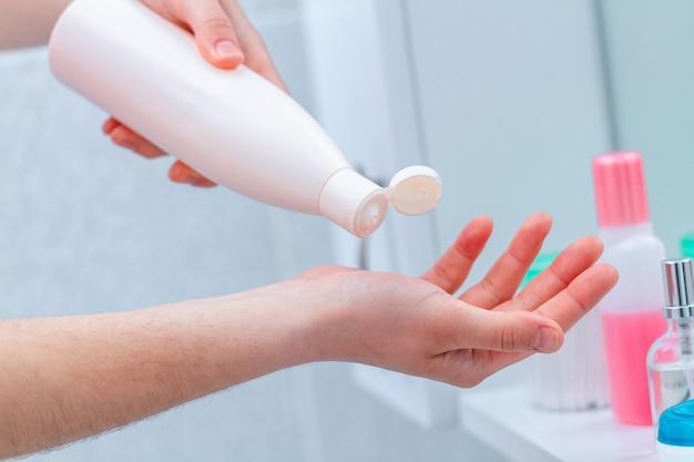 Usando o frasco de creme para a pele seca. aplicar creme corporal hidratante e nutritivo no banheiro de casa. nutrição da pele.