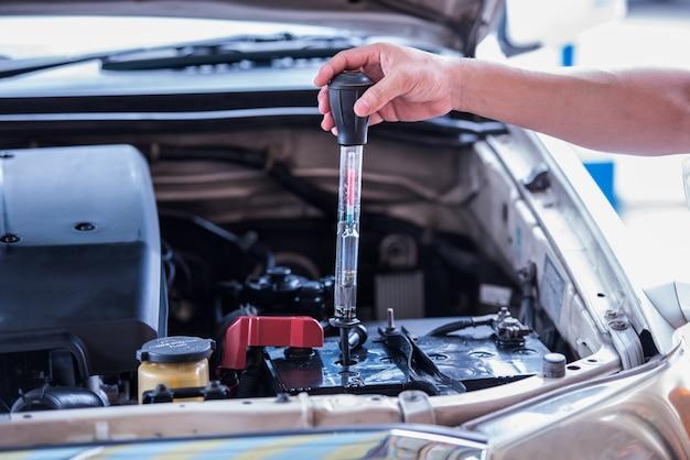 Usando o hidrômetro da bateria medindo a gravidade da bateria de água destilada