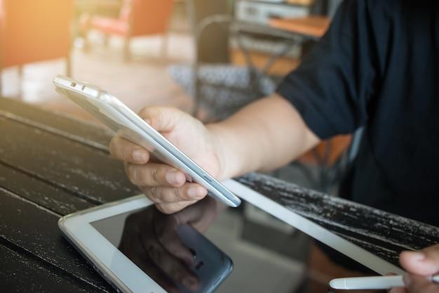 Usando o pagamento bancário on-line por tecnologia de rede internet em desenvolvimento sem fio aplicativo de sincronização de smartphone móvel e tablet com caneta de toque para empresa segurando telefone inteligente para comprar café