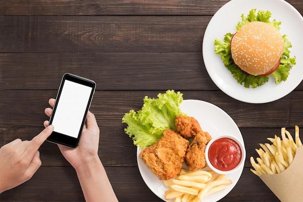 Usando o smartphone com hambúrguer, batatas fritas e frango frito em fundo de madeira