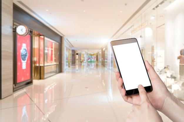 Usando o smartphone em um mercado ou loja de departamento, close up