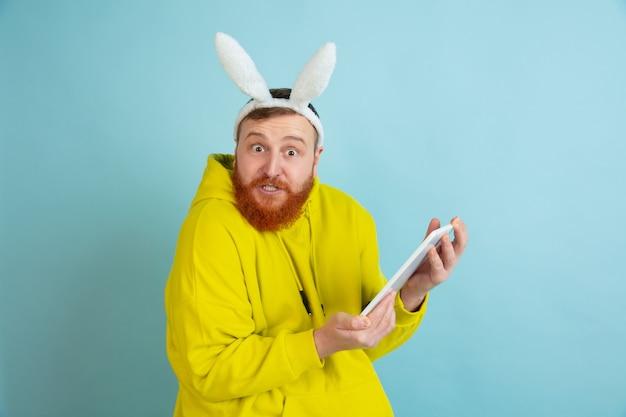 Usando o tablet. homem caucasiano como um coelhinho da páscoa com roupas casuais brilhantes sobre fundo azul do estúdio.