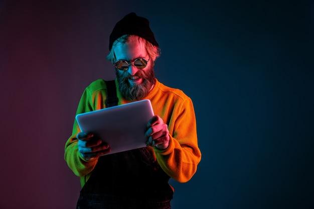 Usando o tablet, jogando. retrato do homem caucasiano em fundo gradiente de estúdio em luz de néon. lindo modelo masculino com estilo hippie. conceito de emoções humanas, expressão facial, vendas, anúncio.