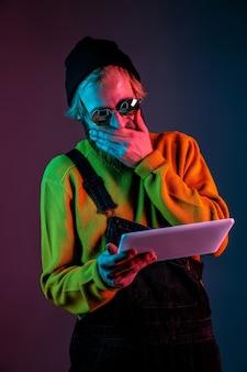 Usando o tablet, parece chocado. retrato de homem branco em espaço gradiente em luz neon