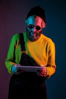 Usando o tablet, parece feliz. retrato do homem caucasiano em fundo gradiente de estúdio em luz de néon. lindo modelo masculino com estilo hippie. conceito de emoções humanas, expressão facial, vendas, anúncio.