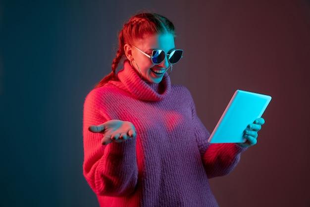 Usando o tablet. retrato da mulher caucasiana isolado no fundo do estúdio gradiente em luz de néon. linda modelo feminino com óculos escuros, cabelo vermelho. conceito de emoções humanas, expressão facial, anúncio.