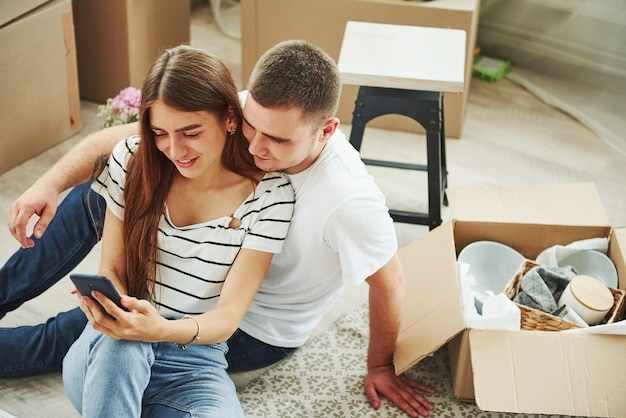 Usando o telefone. casal jovem alegre em seu novo apartamento. concepção de movimento.
