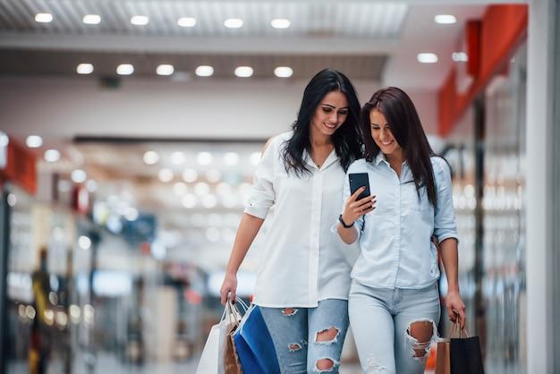 Usando o telefone. duas jovens fazem compras juntas no supermercado.