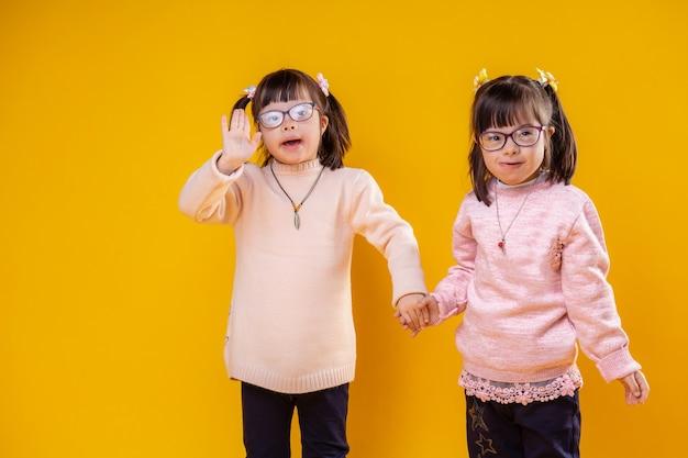 Usando óculos transparentes. garotas fofas sorridentes com anormalidade cromossômica ficando juntas e acenando com as mãos em um gesto de boas-vindas