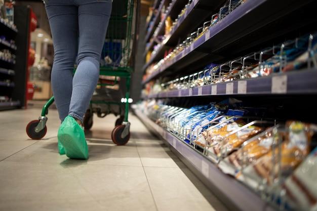 Usando proteção para os pés contra o vírus corona no supermercado