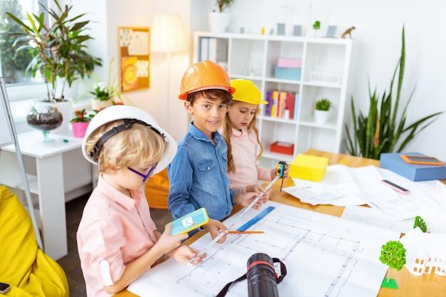 Usando seu smartphone. garoto loiro usando seu smartphone enquanto está perto de colegas fazendo esboços