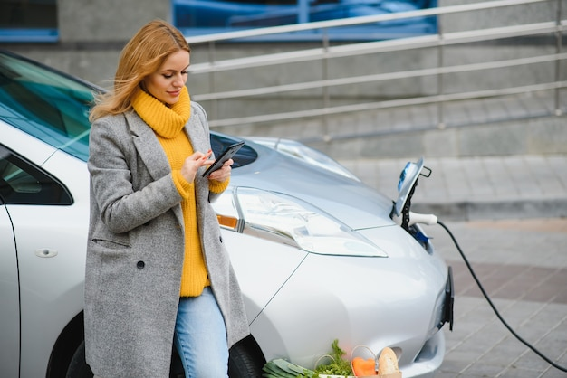 Usando smartphone enquanto espera. mulher na estação de recarga de carros elétricos durante o dia