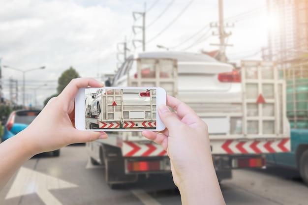 Usando smartphone fotografe o carro quebrado em um caminhão de reboque após acidente de trânsito para seguro de carro